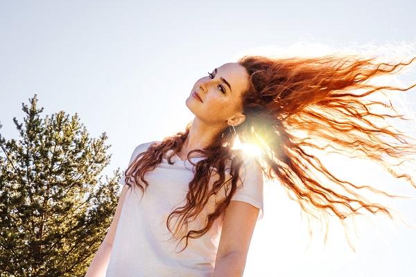 Mulher balançando os cabelos ruivos e longos no ar